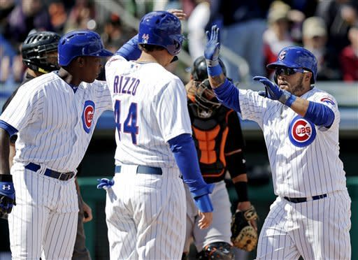Chicago Cubs' Dioner Navarro is congratulated by Anthony Rizzo (44) and Alfonso Soriano after hitting a three-run home run during an exhibition spring training baseball game against the San Francisco Giants, Sunday, Feb. 24, 2013, in Mesa, Ariz. (AP Photo/Morry Gash)