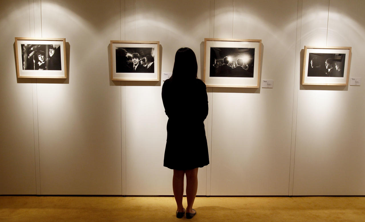 A Christie's employee looks at Mike Mitchell's photographs of The Beatles where his collection is being exhibited at a hotel in London, Friday, June 10, 2011. The previously unseen photographs by US photographer Mike Mitchell were taken during the1964 visit to America. The collection of 50 pictures entitled 'Beatles Illuminated' is expected to realise 100,000 US Dollars (61,500 pounds) when they are auctioned in New York on July 20. (AP Photo/Kirsty Wigglesworth)