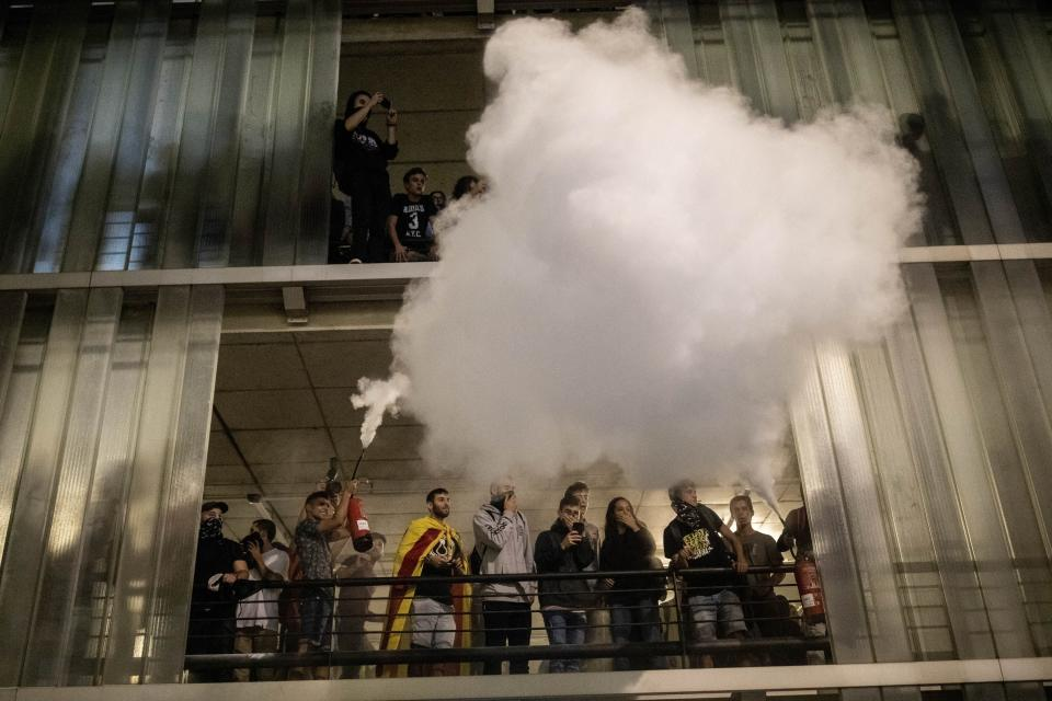 A protester uses a fire extinguisher against police, not pictured, during a demonstration at El Prat airport, outskirts of Barcelona, Spain, Monday, Oct. 14, 2019. Spain's Supreme Court on Monday sentenced 12 prominent former Catalan politicians and activists to lengthly prison terms for their roles in a 2017 bid to gain Catalonia's independence, sparking protests across the wealthy Spanish region. (AP Photo/Bernat Armangue)