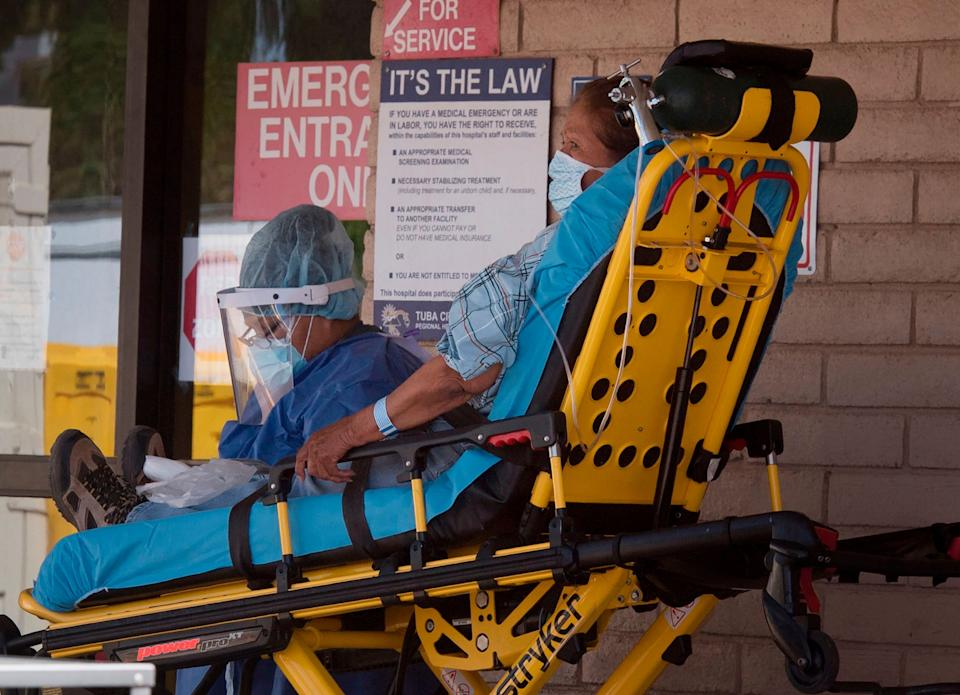 A patient is taken from an ambulance into a hospital in the Navajo Nation town of Tuba City during a 57-hour curfew, imposed to try to stop the spread of the COVID-19 virus, on May 24, 2020. (Photo: MARK RALSTON/AFP via Getty Images)