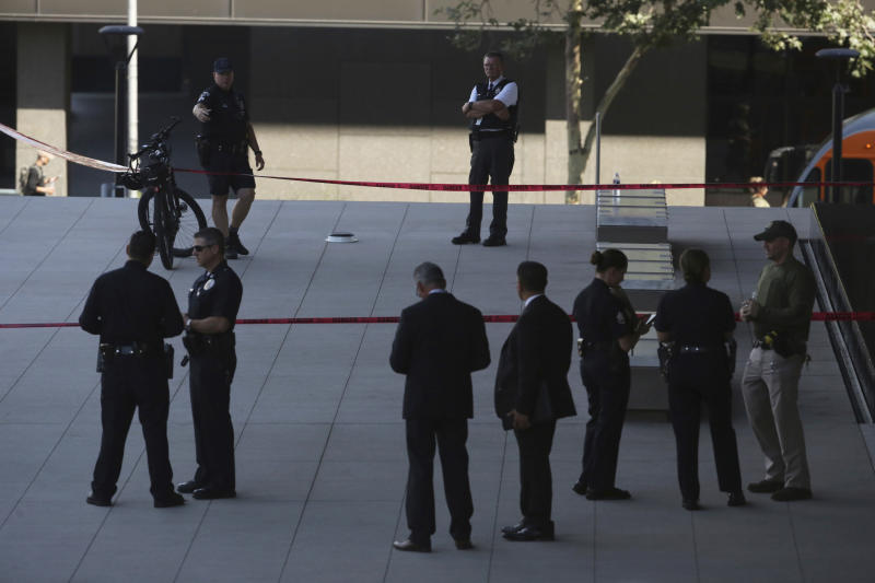 Law enforcement officers from multiple agencies stand at the scene of a shooting outside the federal courthouse in downtown Los Angeles, Tuesday, July 23, 2019. Authorities say a man with a knife was shot and wounded by a courthouse security officer. (AP Photo/Reed Saxon)