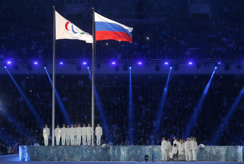 The Paralympic flag (L), is seen besides the Russian national flag during the opening ceremony of the 2014 Paralympic Winter Games. (Reuters)