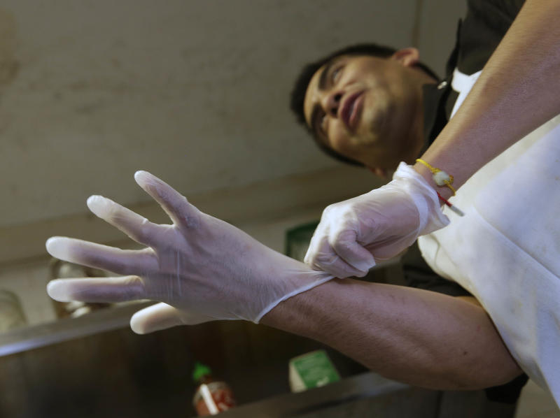 "Luis Escamilla puts on gloves before cutting prosciutto at the Hock Farm Restaurant in Sacramento, Calif. at the Hock Farm restaurant in Sacramento, Calif. Under a bill signed last year by Gov. Jerry Brown, chefs and bartenders in California must keep bare hands off food going straight to the plate or the drink glass, and must use gloves or kitchen utensils such as tongs. California, where the law took effect Jan. 1 and will begin enforcement starting in July, will join 41 other states banning bare-hand contact with ready-to-eat food. In February,after receiving a petition from bartenders calling for an exemption for the ""disposable glove law"" the law's author, Assemblyman Richard Pan, D-Sacramento, a pediatrician, has introduced a bill to repeal the new regulation and revisit the entire issue.(AP Photo/Rich Pedroncelli)"