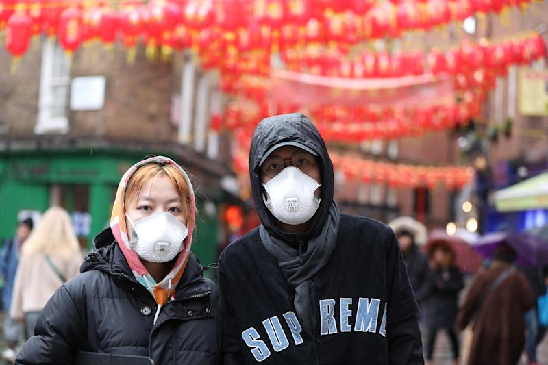 A man and a woman wear face masks on Newport Place in Soho, London, as the first case of coronavirus has been confirmed in Wales and two more were identified in England - bringing the total number in the UK to 19. (PA)