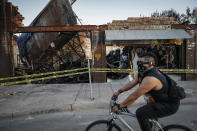 FILE - In this June 1, 2020, file photo, a cyclist passes burned-out businesses along East Lake Street that were destroyed in protests two nights earlier in Minneapolis. Nearly a year after sometimes violent protests for racial justice shook Minneapolis, the immigrant corridor is struggling to recover. Lake Street, which was the focus of much violence during the protests that followed George Floyd's death in police custody, has been a beacon for immigrants for more than a century. (AP Photo/John Minchillo)