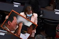 Lawmakers sported masks and bore portraits of revolutionary hero Simon Bolivar and late socialist president Hugo Chavez (pictured here)