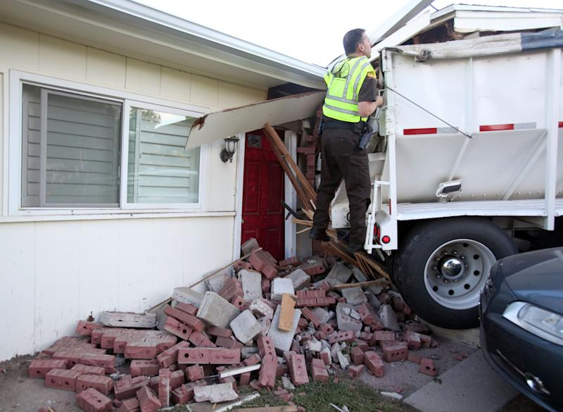Utah Highway Patrol trooper Doug Whitlock inspect a trailer that crushed a vehicle before hitting a home, Thursday, Sept. 5, 2013, in Bountiful, Utah. Bountiful police Sgt. Andrew Bryson says the truck's brakes went out and it rolled about half a block until it came to rest partly inside a house. No one was injured in the accident. (AP Photo/Standard-Examiner, Nick Short) TV OUT; MANDATORY CREDIT