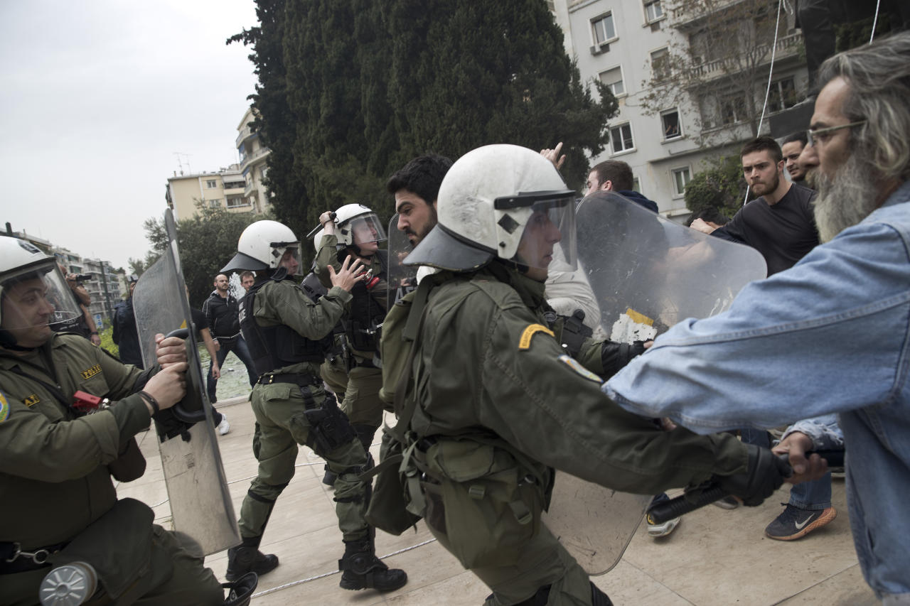 Supporters of the Greek Communist party clash with riot police as they try to pull down a statue of U.S. President Harry S. Truman during a protests against U.S.-led airstrikes in Syria, in central Athens on Monday, April 16, 2018. Police used tear gas to disperse the protesters and the statue was not damaged. (AP Photo/Petros Giannakouris)