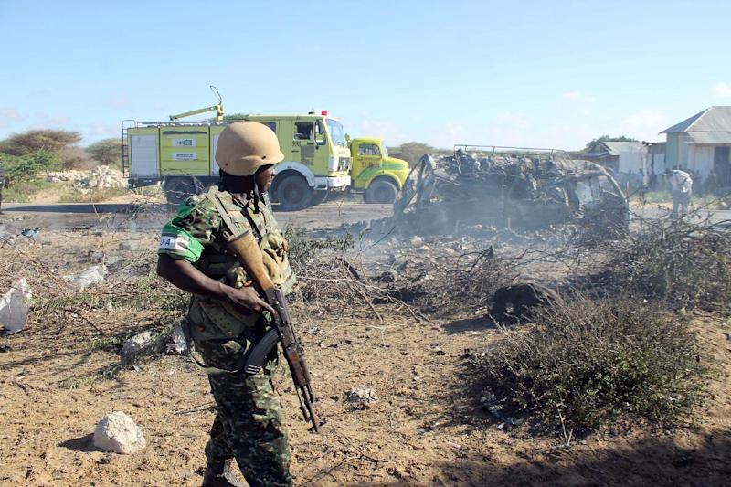 An AMISOM soldier stands guard close to destroyed vehicles following a suicide attack which targeted a convoy of African Union troops on September 8, 2014, near the town of Afgoye