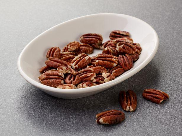 <p>Spread ½ cup pecans out on a microwave-safe dish and microwave until they smell toasted and are dark brown, 4 to 6 minutes.</p>