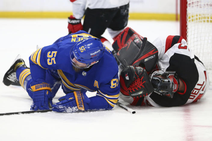 Buffalo Sabres defenseman Rasmus Ristolainen (55) and New Jersey Devils goalie Aaron Dell (47) collide during the second period of an NHL hockey game Thursday, April 8, 2021, in Buffalo, N.Y. (AP Photo/Jeffrey T. Barnes)