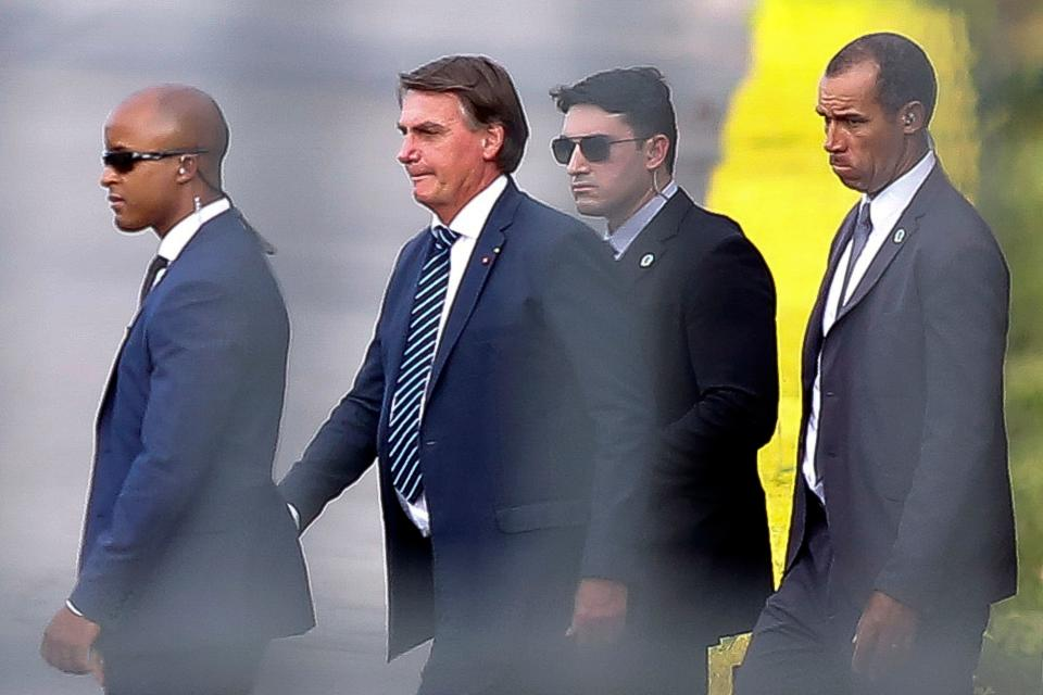 Brazilian President Jair Bolsonaro (C) leaves after greeting supporters in the garden of the Alvorada palace, in Brasilia, on January 22, 2021. - Brazil received on Friday a first batch with two million doses of the Oxford / AstraZeneca vaccine developed by the Institute of Serum from India. (Photo by Sergio Lima / AFP) (Photo by SERGIO LIMA/AFP via Getty Images)