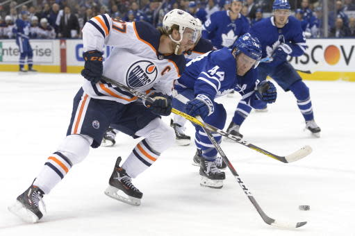 Edmonton Oilers centerConnor McDavid (97 shoots under pressure from Toronto Maple Leafs defenseman Morgan Rielly (44) during first-period NHL hockey game action in Toronto, Monday, Jan. 6, 2020. (Nathan Denette/The Canadian Press via AP)