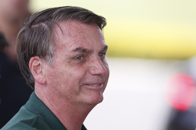 Brazil's President Jair Bolsonaro speaks to supporters outside his official residence, Alvorada Palace, as he arrives to spend New Year's with family in Brasilia, Brazil, Tuesday, Dec. 31, 2019. Heading into his second year as president, Bolsonaro has held firm to his combative culture-warrior policies while feuding with critics at home and abroad — an approach that has thrilled supporters but eroded his efforts to win allies and lift the world's 9th-largest economy out of its doldrums. (AP Photo /Eraldo Peres)