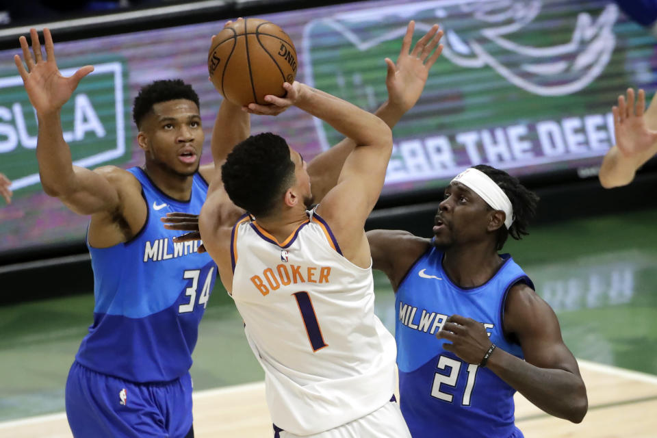Phoenix Suns' Devin Booker, center, is fouled as he shoots between Milwaukee Bucks' Jrue Holiday, right, and Giannis Antetokounmpo, left, during the first half of an NBA basketball game Monday, April 19, 2021, in Milwaukee. (AP Photo/Aaron Gash)
