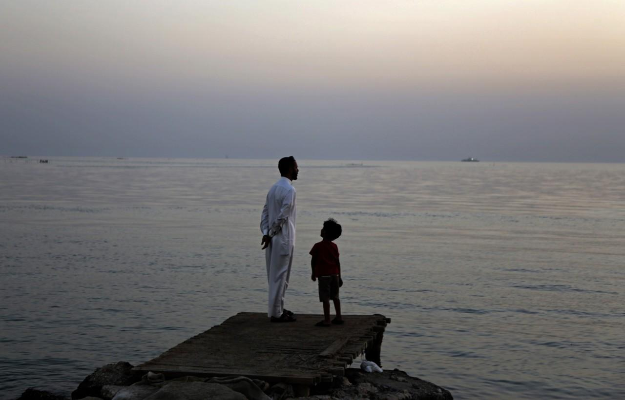 <p>A Bahraini man and his son look for the new moon that marks the start of the Islamic holy month of Ramadan along the Persian Gulf coast, in Karzakan, Bahrain, June 5, 2016. (AP/Hasan Jamali) </p>