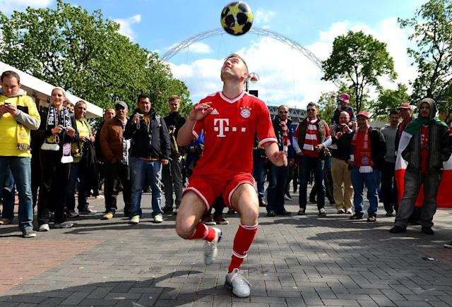 A Bayern Munich football trickster peforms outside Webley Stadium before the game.