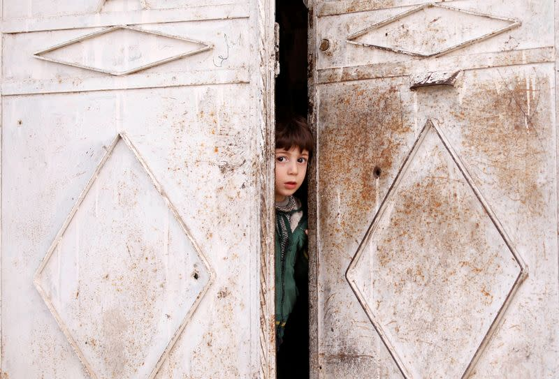Seham Hamu's grandson looks out from a door in Douma