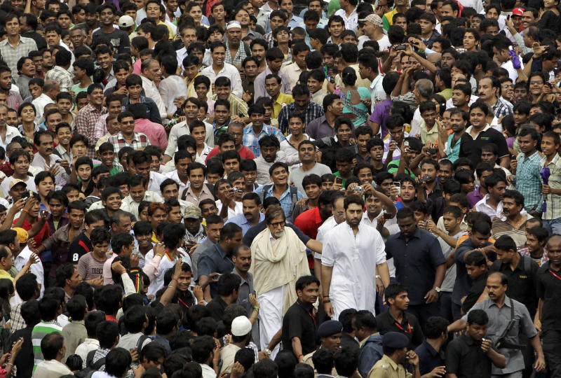 Bollywood superstar Amitabh Bachchan, center and his son actor Abhishek Bachchan, center right, walk through a sea of fans and mourners to attend the funeral of Rajesh Khanna in Mumbai, India, Thursday, July 19, 2012. Khanna, whose success as a romantic lead in scores of Indian movies made him Bollywood's first superstar, died Wednesday after a brief illness. He was 69. (AP Photo/ Rajanish Kakade)