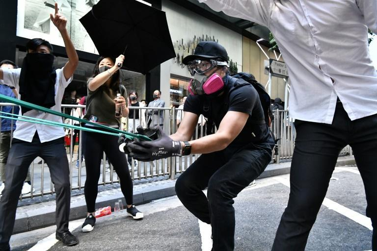 A protester uses an improvised catapult to fire a missile against police in the Central district of Hong Kong