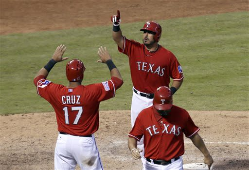 Texas Rangers' Geovany Soto, top, is greeted at the plate by Nelson Cruz (17) after hitting a three-run home run that scored Cruz and Lance Berkman, bottom, in the sixth inning of a baseball game against the Houston Astros Saturday, July 6, 2013, in Arlington, Texas. The shot came off a pitch from Astros relief pitcher Wesley Wright. (AP Photo/Tony Gutierrez)