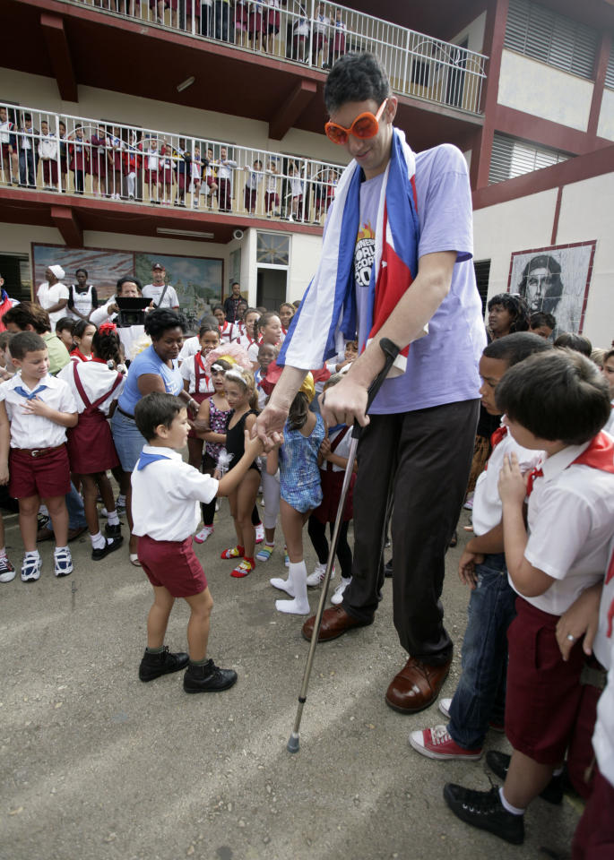Sultan Kosen, top, of Turkey, who according to the Guinness World Record Association is the world's tallest man, greets students during a visit to the Cesareo Fernandez school in Havana, Cuba, Monday, March 14, 2011. Kosen, 28, is part of a group of young people visiting Cuba with Cuba Amore Foundation, a solidarity organization.