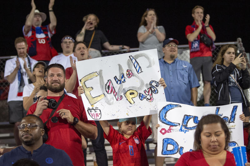 A young United States fan holds up a sign advocating for equal pay for women's soccer players after the United States defeated Japan  in a SheBelieves Cup women's soccer match, Wednesday, March 11, 2020 at Toyota Stadium in Frisco, Texas. (AP Photo/Jeffrey McWhorter)