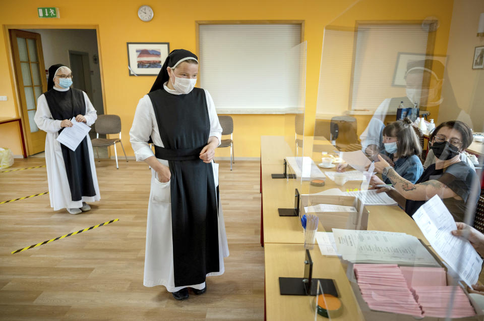 Sisters Pauline, left, and Gertrud from the Cistercian convent of Helfta arrive at the polling station during the state elections of German federal state Saxony-Anhalt, in the Helfta district of Eisleben, Germany, Sunday, June 6, 2021. The election for the new state parliament in Saxony-Anhalt is the last state election before the federal election in September 2021. (Hendrik Schmidt/dpa via AP)