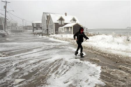 A woman runs from the surf as waves crash into houses on Lighthouse Road during a winter nor'easter snow storm in Scituate, Massachusetts January 3, 2014. REUTERS/Dominick Reuter