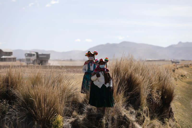 Women walk through fields and near a highway in the Carata peasant community, in Puno