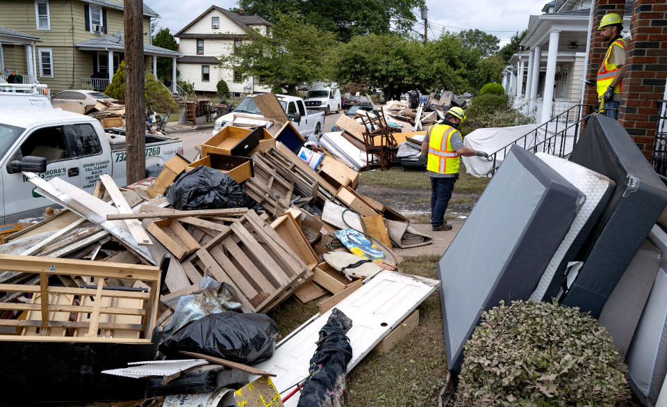 Utility workers work among debris from flood damage caused by the remnants of Hurricane Ida in Manville, N.J., Sunday, Sept. 5, 2021. Flood-stricken families and business owners across the Northeast are hauling waterlogged belongings to the curb and scraping away noxious mud as cleanup from Ida moves into high gear. (AP Photo/Craig Ruttle)