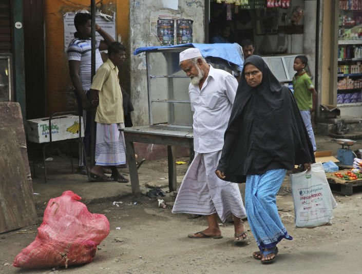 """A Sri Lankan Muslim woman walks across a market in Colombo, Sri Lanka, Monday, April 29, 2019. The Catholic Church in Sri Lanka said Monday that the government should crack down on Islamic extremists with more vigor """"as if on war footing"""" in the aftermath of the Easter bombings. Meanwhile, the government has banned all kinds of face coverings that may conceal people's identities. The emergency law, which took effect Monday, prevents Muslim women from veiling their faces. (AP Photo/Manish Swarup)"""
