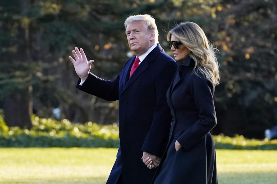 Donald and Melania Trump walk at the White House in December.