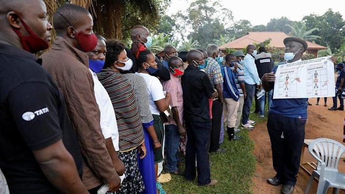 A man holds up a poster on how to mark a ballot paper as people queue at a voting center during the presidential elections in Kampala, Uganda, January 14, 2021.