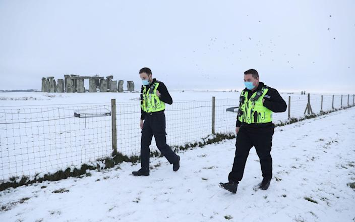 Police at a snowy Stonehenge in Wiltshire - Andrew Matthews/PA