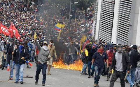 Enraged anti-government demonstrator gather during clashes with the police as they protest against President Lenin Moreno and his economic policies - Credit: Fernando Vergara/AP