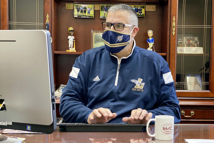 """In this November 2020 photo, provided by Eugene """"Geno"""" Thomas, Thomas, superintendent of the Lowellville, Ohio, School District, works in his office. Contact tracing and isolation protocols meant to contain the spread of the coronavirus are sidelining school employees and frustrating efforts to continue in-person learning. """"It boils down to the staff,"""" Thomas said. """"If you can't staff a school, you have to bring it to remote."""" (Courtesy of Eugene Thomas via AP)"""