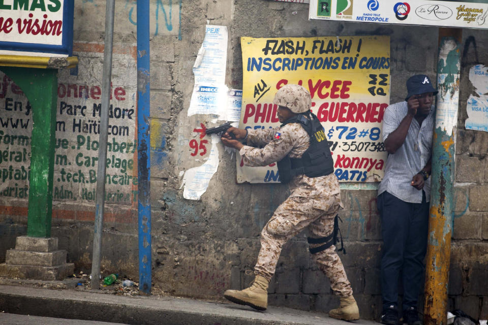 A police officer points his gun at residents of Delmas 95 district during a protest to demanding the resignation of Haiti's president Jovenel Moise in Port-au-Prince, Haiti, Monday, Nov. 18, 2019. At least four people were shot and wounded during a small protest in Haiti's capital after a speech by embattled President Jovenel Moise. A local journalist, a police officer and two protesters were rushed away with apparent bullet wounds. (AP Photo/Dieu Nalio Chery)