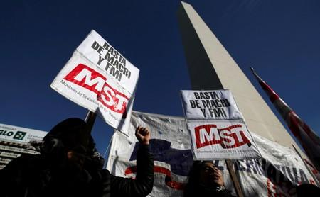 """FILE PHOTO: Demonstrators hold placards that reads """"enough of (Argentina's President) Macri and IMF"""", at the Buenos Aires Obelisk during a one-day national strike"""
