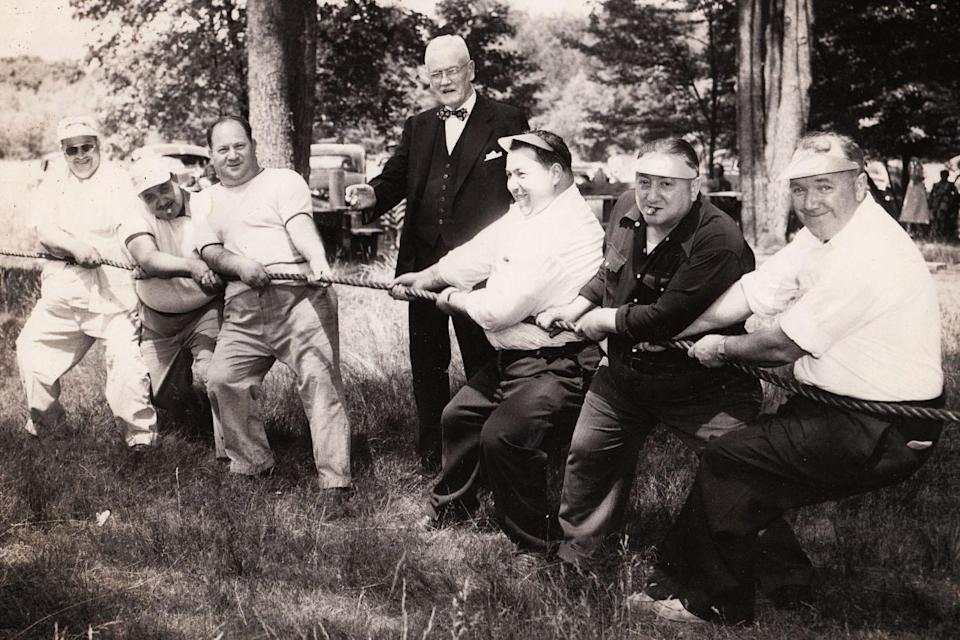 """<div class=""""cell medium-auto caption""""> Tug of war at the summer outing of a Massachusetts Fat Men's Club in 1951</div> <div class=""""cell medium-shrink medium-text-right credit"""">Harry Bagan Photographs, Cambridge Historical Commission</div>"""