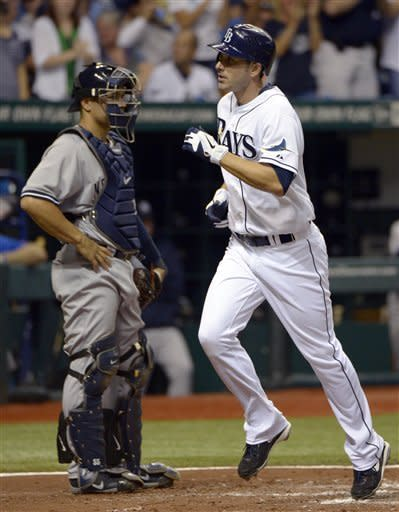 Tampa Bay Rays' Matt Joyce, right, runs past New York Yankees catcher Russell Martin after hitting a solo home run during the third inning of a baseball game in St. Petersburg, Fla., Saturday, April 7, 2012.(AP Photo/Phelan M. Ebenhack)