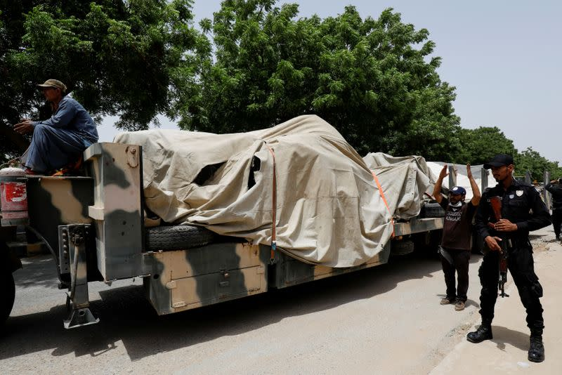 FILE PHOTO: Police officer stands guard beside a truck loaded with the wreckage of the crashed plane, in Karachi