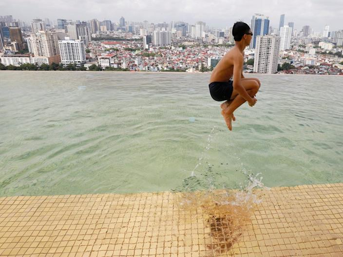 A boy jumps into the water at the gold-plated infinity pool of the Dolce Hanoi Golden Lake luxury hotel in Hanoi, Vietnam, on July 2, 2020.