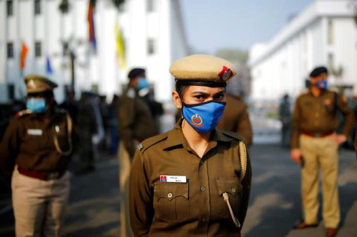 Police officer stands guard out of a venue where farmer leaders meet with government representatives in New Delhi
