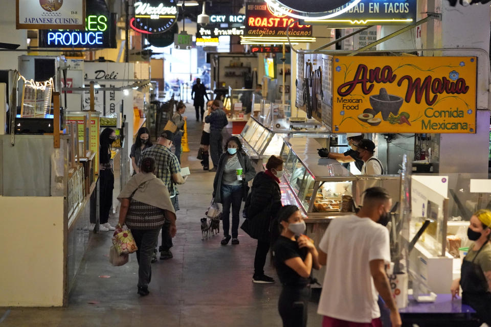 Customers walk the aisles at the Grand Central Market Monday, Nov. 16, 2020, in Los Angeles. California Gov. Gavin Newsom announced Monday, Nov. 16, 2020, that due to the rise of COVID-19 cases, Some counties have been moved to the state's most restrictive set of rules, which prohibit indoor dining. The new rules begin, Tuesday, Nov. 17. (AP Photo/Marcio Jose Sanchez)