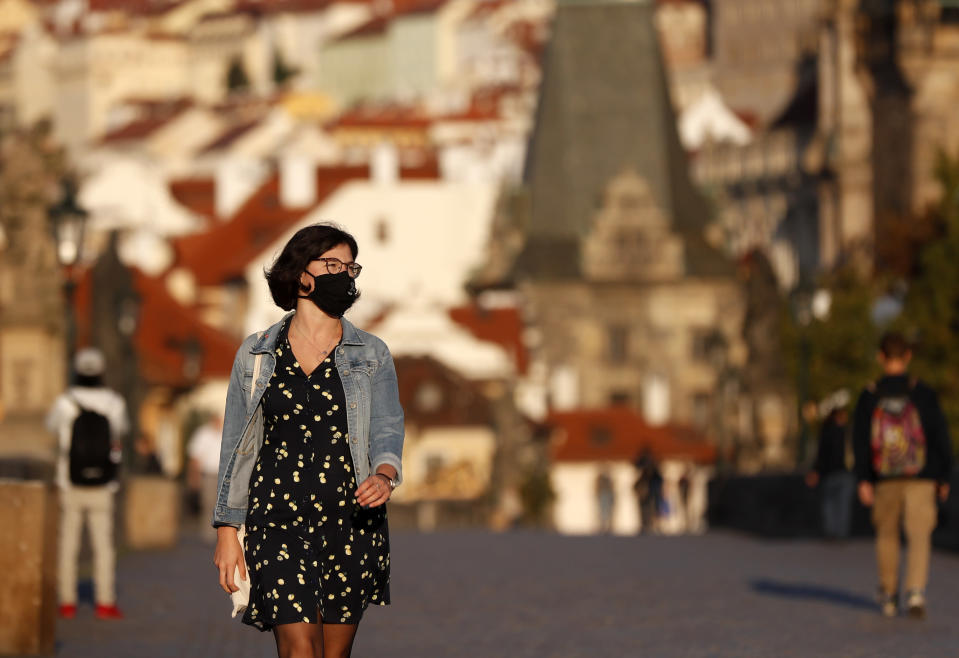 A young woman wearing a face mask walks across the medieval Charles Bridge in Prague, Czech Republic, Friday, Sept. 18, 2020. The Czech Republic has been been facing the second wave of infections. The number of new confirmed coronavirus infections has been setting new records almost on a daily basis, currently surpassing 3,000 cases in one day for the first time. (AP Photo/Petr David Josek)