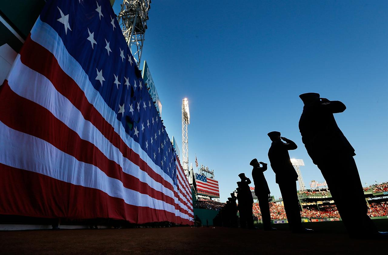BOSTON, MA - MAY 27: Airmen from the Hanscom Air Force Base stand and salute in front of the large American flag unfurled over the Green Monster during the singing of the national anthem prior to the interleague game between the Boston Red Sox and the Philadelphia Phillies on Memorial Day on May 27, 2013 at Fenway Park in Boston, Massachusetts. (Photo by Jared Wickerham/Getty Images)