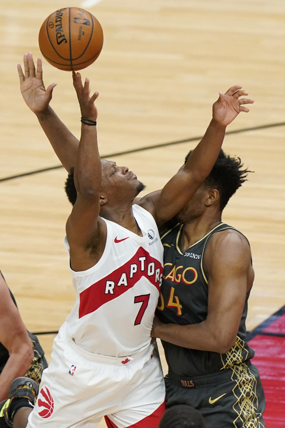 Toronto Raptors guard Kyle Lowry, left, shoots against Chicago Bulls center Wendell Carter Jr., during the second half of an NBA basketball game in Chicago, Sunday, March 14, 2021. (AP Photo/Nam Y. Huh)