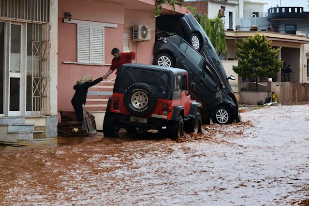 <p>A man helps evacuate a woman from a flooded street in Mandra, northwest of Athens, on Nov. 16, 2017. (Photo: Dimitris Lambropoulos/AFP/Getty Images) </p>