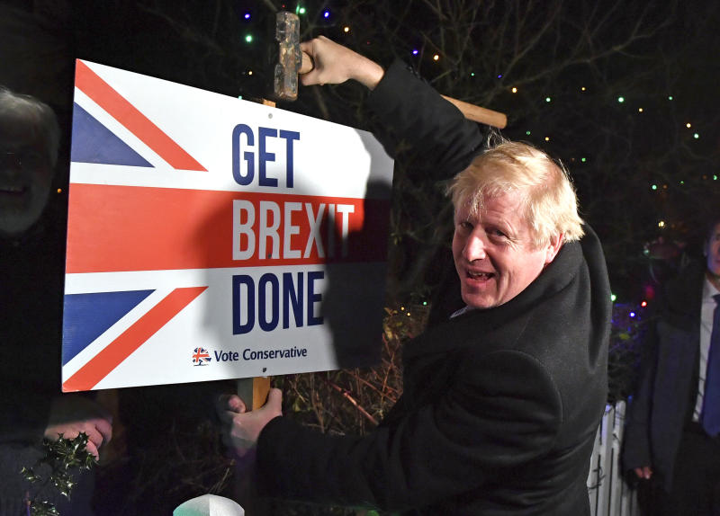 "Britain's Prime Minister and Conservative party leader Boris Johnson poses as he hammers a ""Get Brexit Done"" sign into the garden of a supporter, in Benfleet, east of London on Wednesday, Dec. 11, 2019, the final day of campaigning for the general election. Britain goes to the polls on Thursday. (Ben Stansall/Pool Photo via AP)"